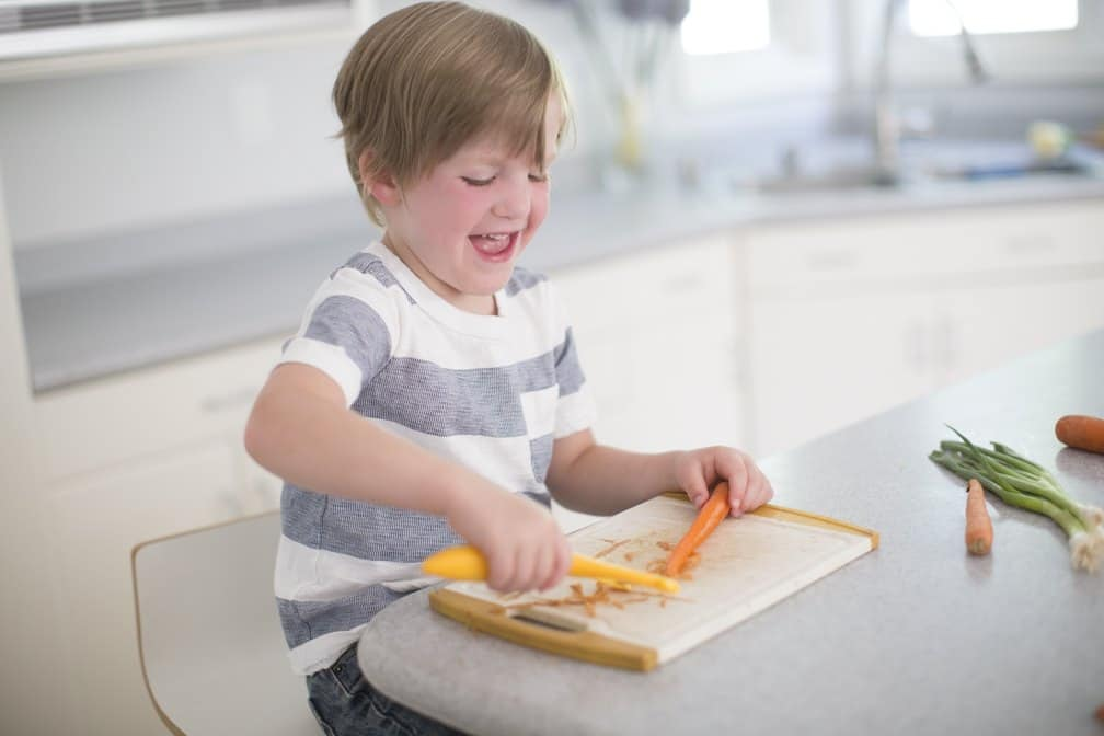 child peeling carrot