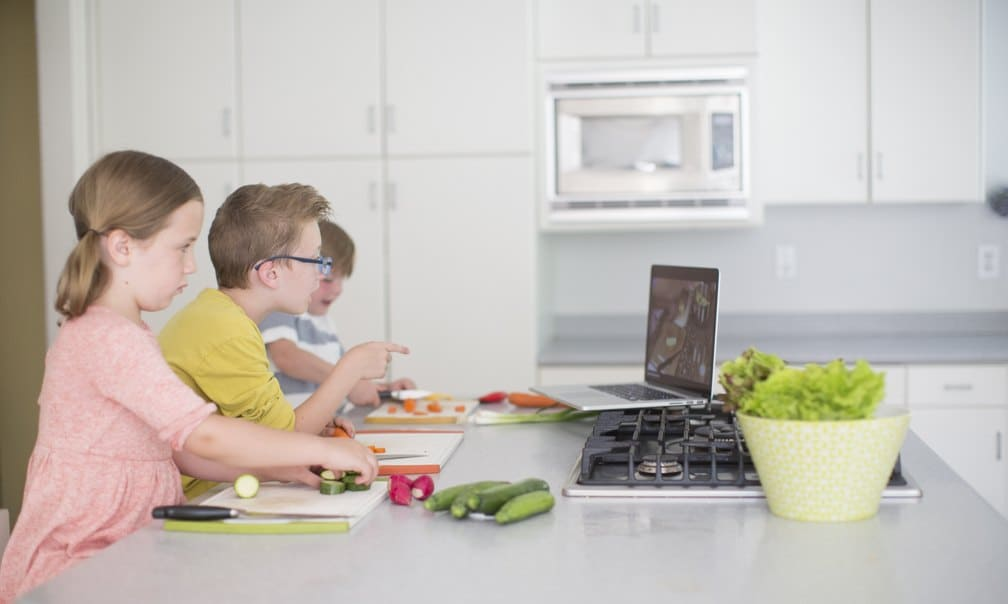 Kids watching a cooking lesson at a kitchen island
