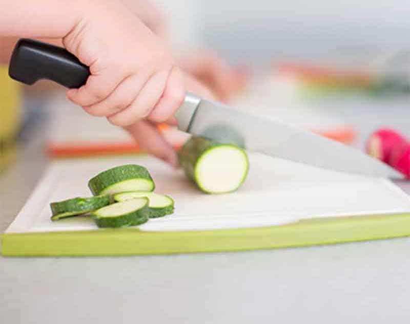 Kid cutting a zucchini