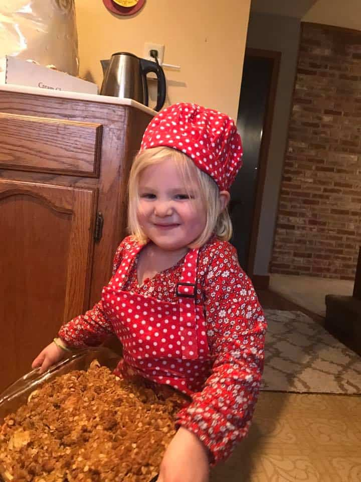 little girl proudly holding food she cooked