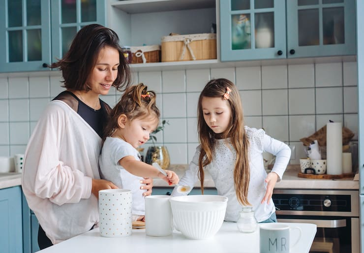 Mom and two daughters cook together in the kitchen