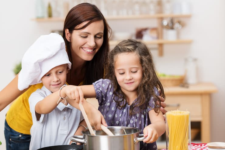 happy kids learning to cook in kitchen with smiling mom