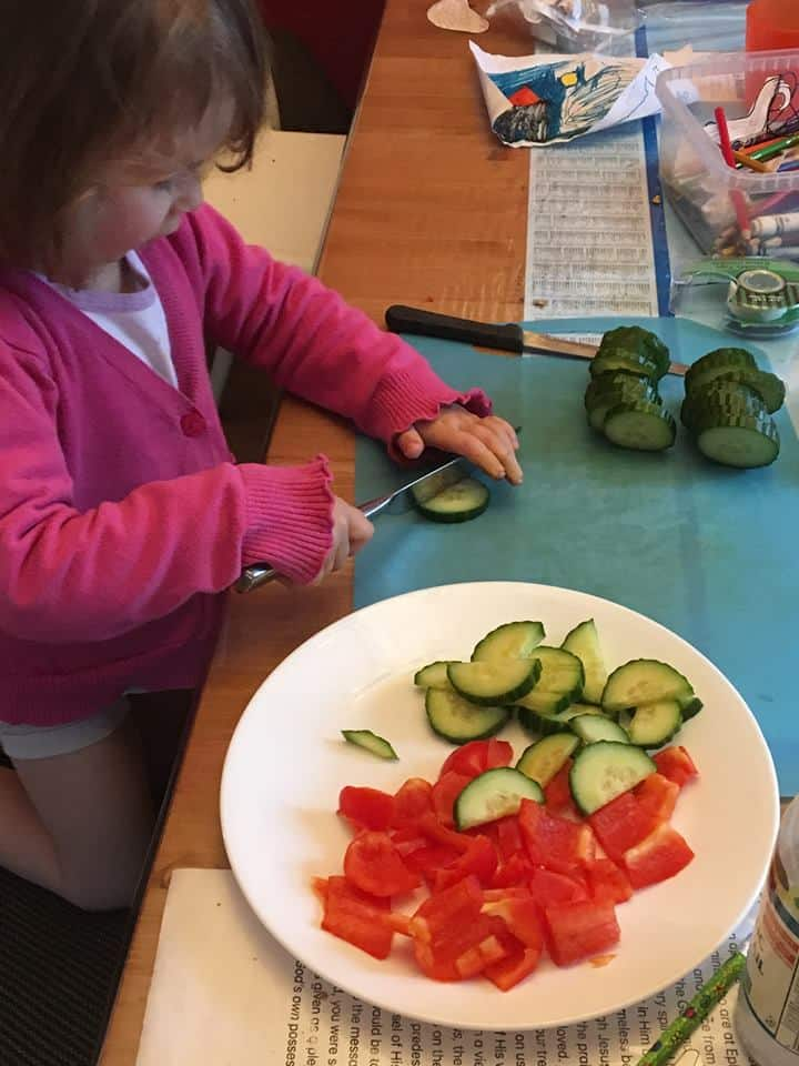 2yo cutting cucumbers and red peppers with a butter knife