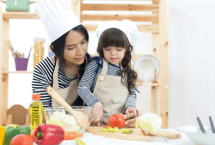 mom teaching happy child to cook and cut veggies
